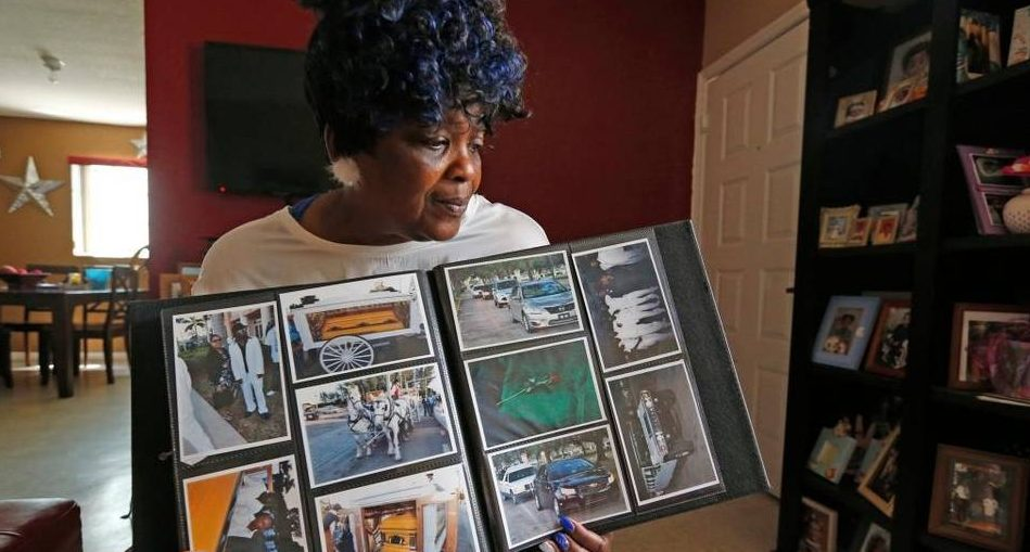 Dorthy Ruffin holds the scrapbook from her grandson's funeral, which reflected the child's interests and passions, on April 11, 2016. Her grandson, Marlon Eason 10, was killed by a stray bullet on his porch in Overtown. Photo courtesy of The Miami Herald.