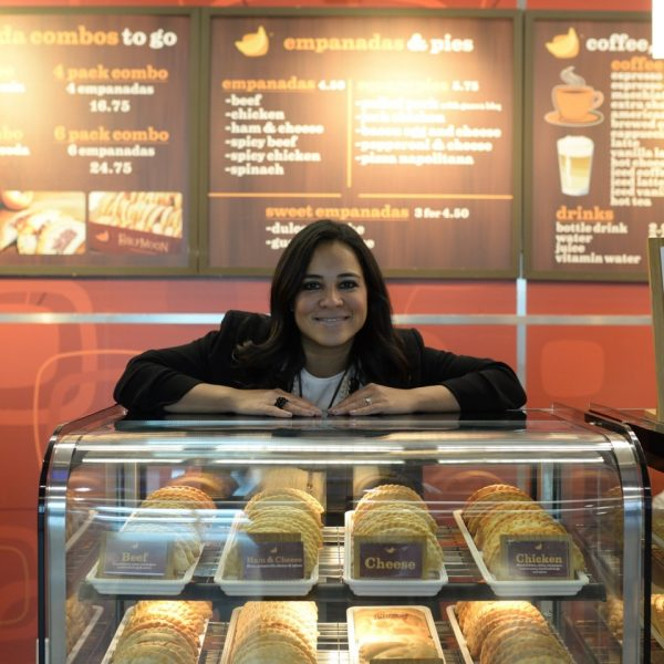 Pilar Guzman, CEO and owner of Half Moon Empanadas, stands behind the business's display case at Miami International Airport.