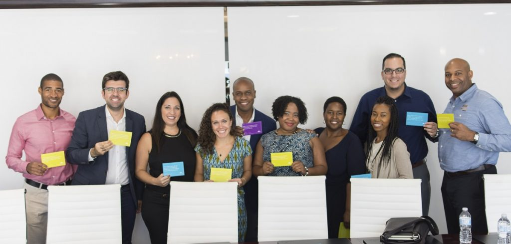 Pictured above: Former Foundation Trustee Marlon Hill, past and current Miami Fellows and other community young leaders hold up fact cards they selected as part of their 2017 My Miami Story conversation.