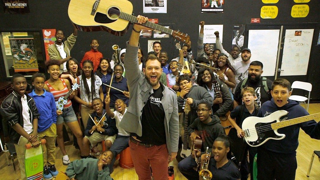 Chad Bernstein holding guitar with Guitars Over Guns students